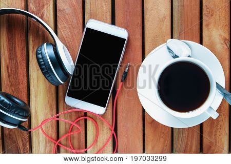 Smartphone headphones with coffee espresso cup hot on a wooden table . Top view