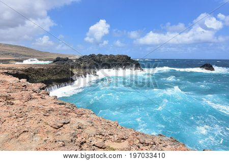 Water running down the rock sea cliffs by Andicuri Beach in Aruba.
