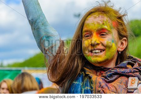 Moscow, Russia - June 3, 2017: Little girl with joyful smile and multi-colored face on summer holiday. Traditional Indian festival of colours Holi turned into fun event in many countries of the world