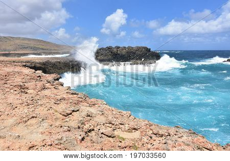 Large wave crashing against the rock bluffs in Aruba.