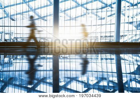 modern building hallway with blurred motion passengers,blue toned,china.