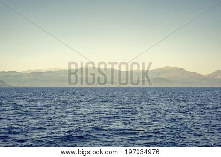 sea, mountains landscape, sailboat sailing far from seashore
