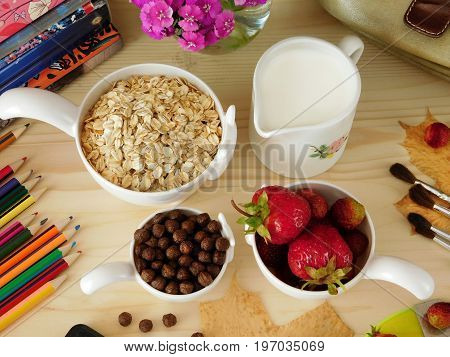 Ingredients for breakfast surrounded by school supplies on a wooden table