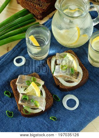 Salted herring with onion on a slice of bread and misted glass vessels filled with drink in the background