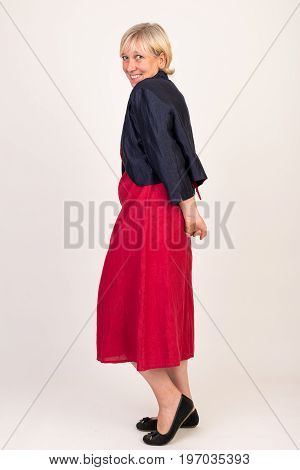 portrait of a attractive blond haired mid aged european woman wearing red dress and black top showing happy face and looking shy - full body - studio shot on white background.