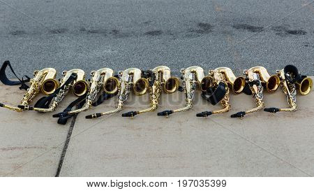 a row of alto saxophones on sidewalk waiting for their ride