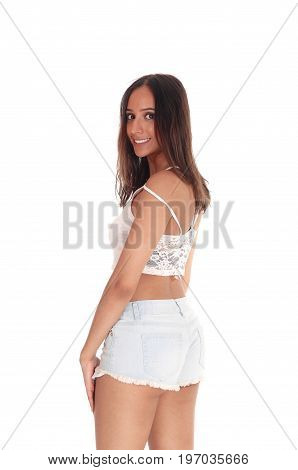 A beautiful young woman in jeans shorts and small top standing from the back looking over her shoulder isolated for white background