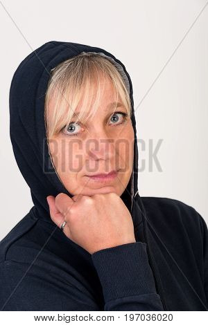 Beautiful european mid aged woman with blonde hair dressed in a black casual hooded jacket looking thoughtful - studio shot in front of a white background