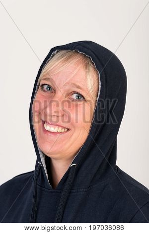 Beautiful european mid aged woman with blonde hair dressed in a black casual hooded jacket looking happy - studio shot in front of a white background