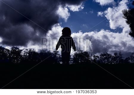 silhouette contrast young boy standing on a hill against a bright background