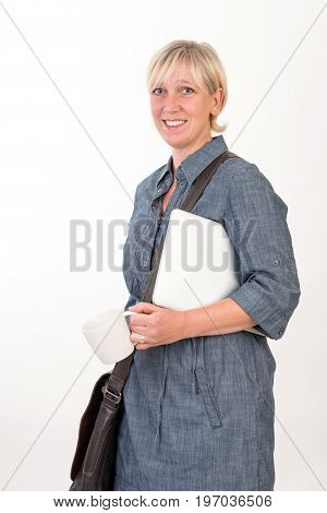 business woman carrying laptop, coffee cup and bag looking happy - studio shot in front of a white background