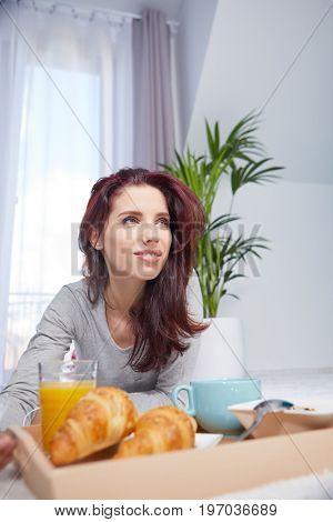 Beautiful happy woman having breakfast in bed