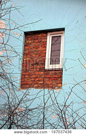 Window and wall with plaster and brick