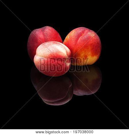 Three ripe nectarines on a black background isolated with real reflection