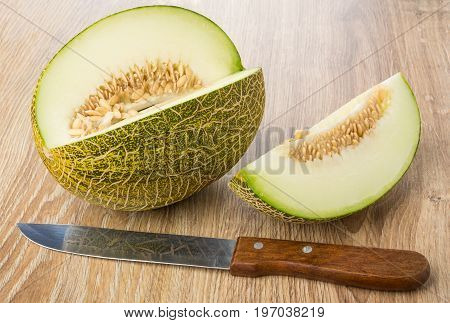 Pieces Of Melon With Seeds And Kitchen Knife On Table