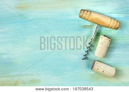 A photo of an old-fashioned corkscrew with corks, shot from above on a teal background texture with a place for text. A design template for a wine list or a tasting invitation