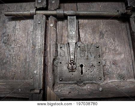 Medieval door lock with keyhole. Ancient wooden door