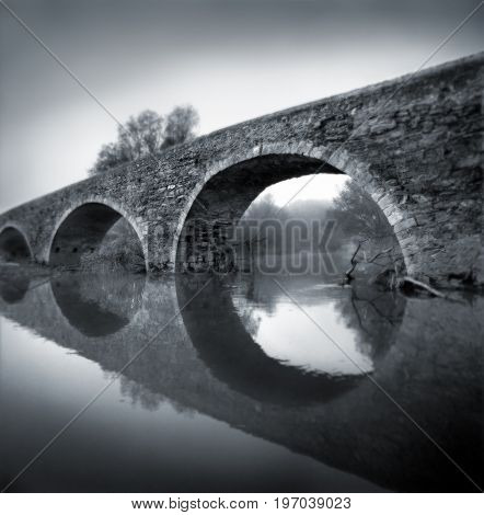 Black and white film photography. Romanesque bridge in a misty environment