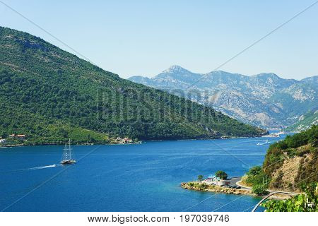View of Boko Kotorska bay in Montenegro on a hot summer day. Vacation on the beach, the morning landscape in the bay. The southernmost fjord of Europe.