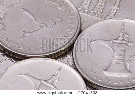 Detail of different United Arab Emirates Dirhams coins on the table.