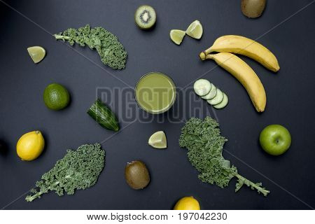 Healthy living concept with a glass of green smoothie surrounded by Kale apples almonds limes and other fruit and veg on a dark background.