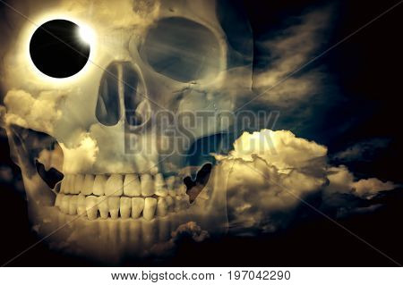 Amazing scientific natural phenomenon. Double exposure of total solar eclipse with diamond ring placed on skull's eye socket combined sky with clouds. Abstract fantastic background.