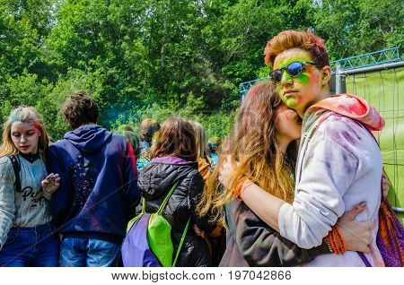 Moscow, Russia - June 3, 2017: Boy and girl, stained with paint, embrace on summer festival of colours Holi. Traditional Indian festival Holi turned into a fun event in many countries of the world