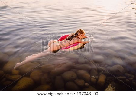 Woman with ideal body swimming on donut in the sea at sunset. Slim lady relaxing on her holidays at ocean