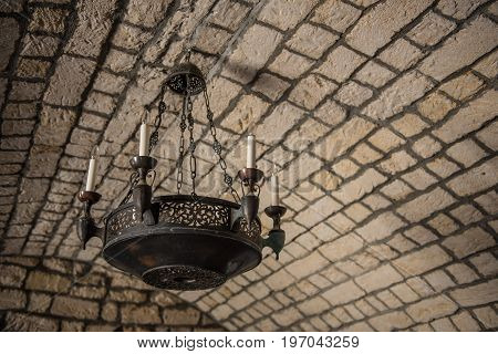An ancient Middle Ages chandelier on a brick castle ceiling