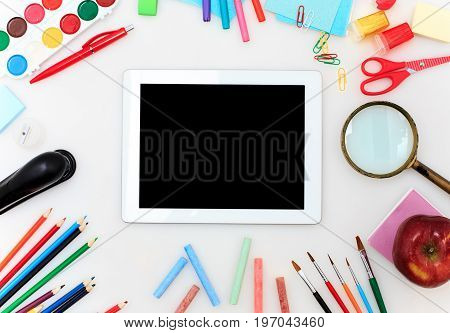 School set with back to school inscription, notebooks, tablet, pencils, brush, scissors and apple on white background