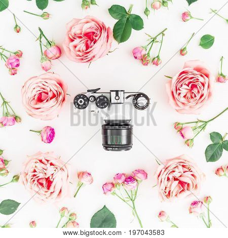 Round frame of pink roses and old retro camera on white background, lifestyle composition. Flat lay, top view.