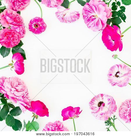 Floral frame of pink roses and leaves with envelope on white background. Flat lay, top view. Floral lifestyle composition.