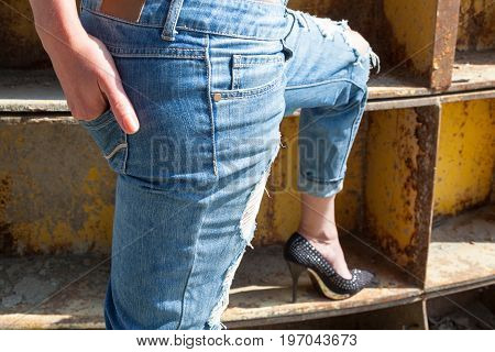 Woman in ragged jeans and black stiletto-heeled shoes near the rusty metal industrial wall. Hand in the back pocket.