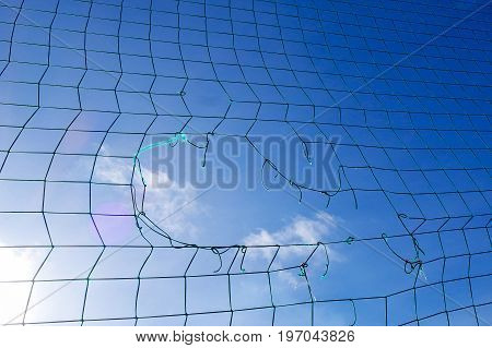 The broken net is outdor. Stadium in spring or summer