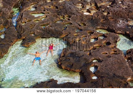 Family beach holiday lifestyle. Happy couple relax in natural sea pool at Angel's Billabong on Pasih Uug. Best travel destinations on Bali island. Nusa Penida day tour popular place. Leisure activity.