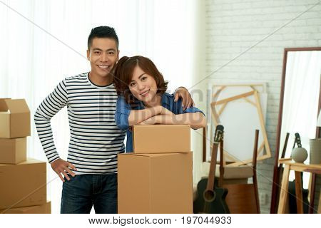 Group portrait of handsome young man gently embracing his girlfriend while she leaning on cardboard box and looking at camera with charming smile, they are ready to move into new apartment