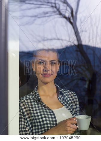 beautiful young woman drinking morning coffee by the window in her home