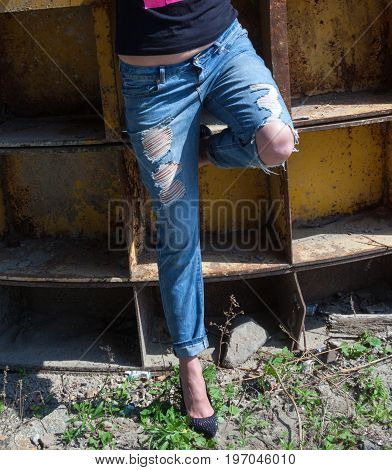 Woman in ragged jeans and black stiletto-heeled shoes near the rusty metal industrial wall.