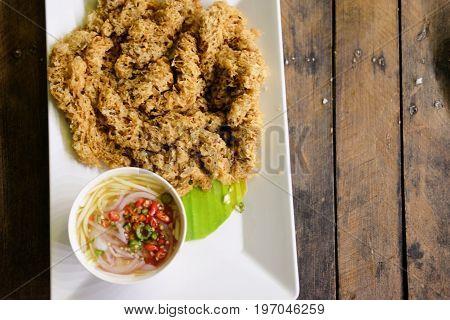 Thai cuisine and food Thai traditional crispy catfish salad on wood table