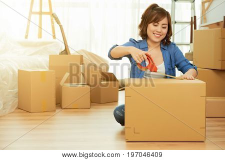 Attractive young woman sitting on floor, packing cardboard box with help of adhesive tape and dreaming about cohabiting with her boyfriend