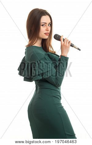 Lovely lady in green dress with microphone isolated on white background