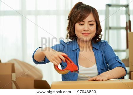 Waist-up portrait of joyful Asian woman packing moving boxes while sitting in living room and dreaming about cohabiting with her boyfriend
