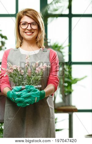 Young florist in rubber gloves