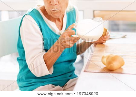 Senior woman hands holding big cup of yogurt. Old woman holding a glass of milk, health care concept, wrinkled skin, no face. Soft focus