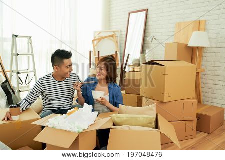 Young Vietnamese couple chatting animatedly with each other and having a bite while taking rest from packing stuff in moving boxes