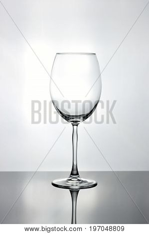 Tall empty isolated curved wine glass with a tall thin stem on a bright white background
