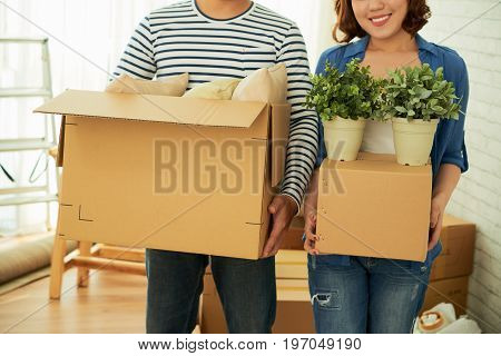 Young couple posing for photography with cardboard boxes in hands while preparing for relocation to new apartment, close-up shot