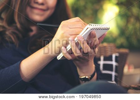 A beautiful Asian woman holding black pencil and writing on notebook sitting in modern cafe with blur green vertical garden background