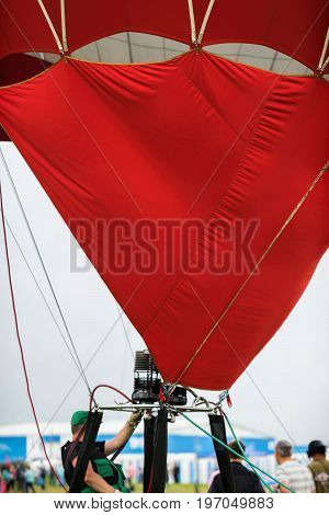 Hot Air Balloon pilot with an unrecognizable face before the flight, sitting in the basket, maintains the required pressure in the balloon with the help of a burner. Close-up of part of hot air balloon, people around