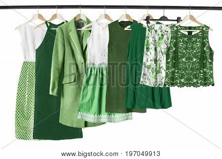 Set of green woman clothes on clothes racks on white background